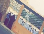 صورة تجسد حنان أم تراقب طفلها خلف سور المدرسة في يومه الأول